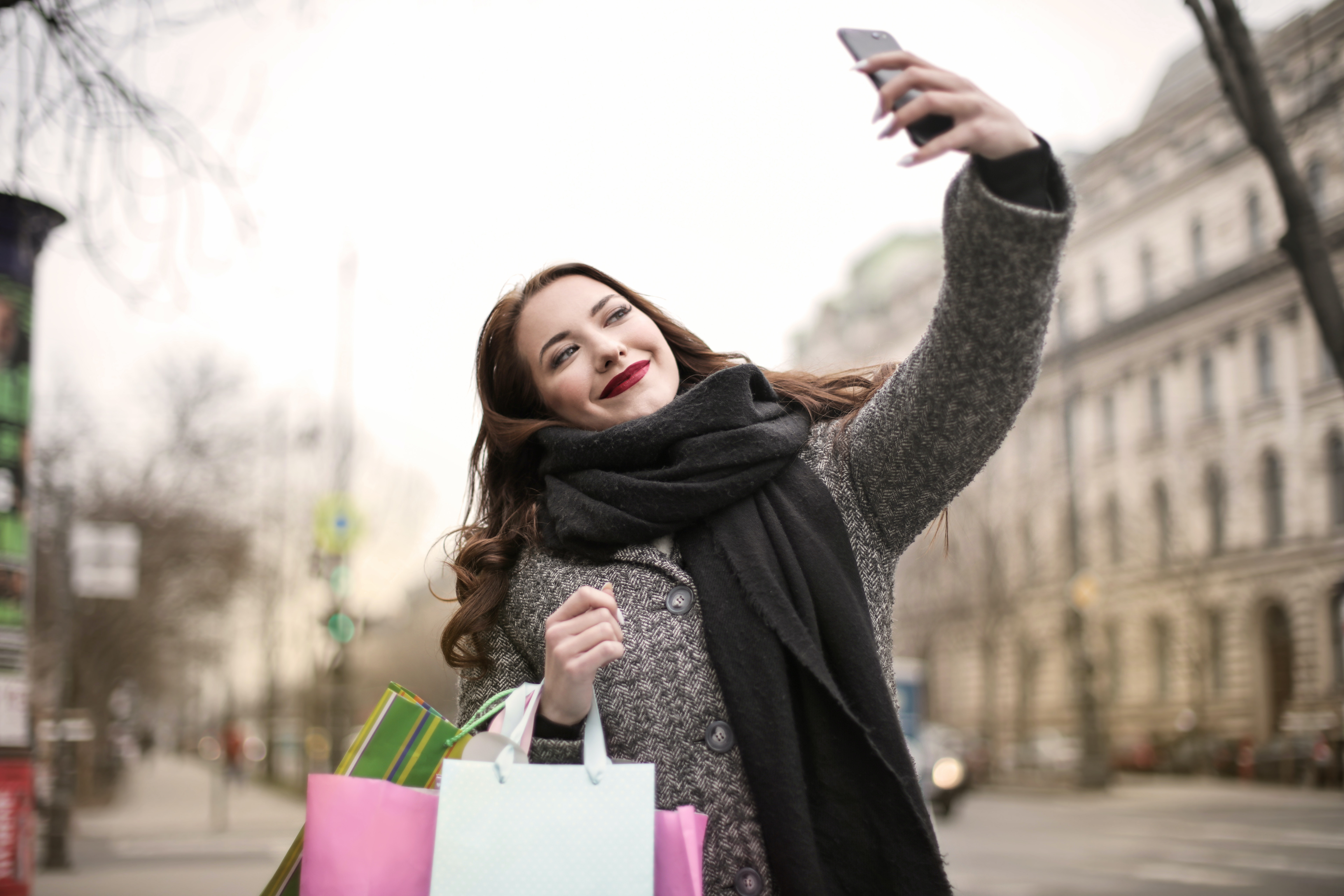 Girl holding shopping bags and taking a selfie